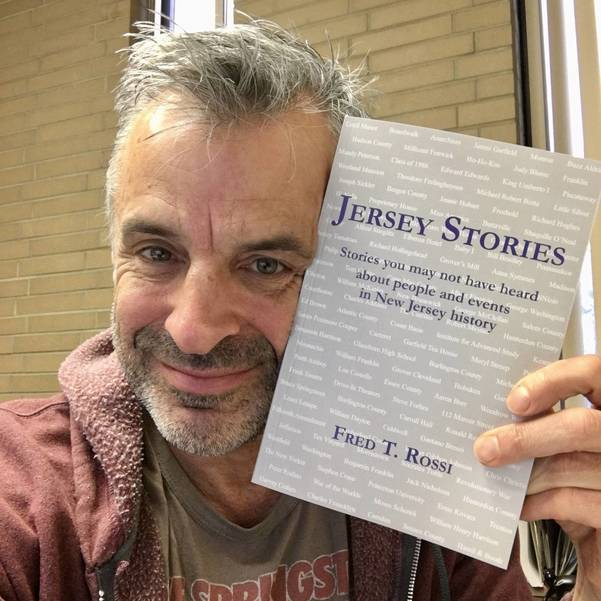 Fred Rossi holds his book